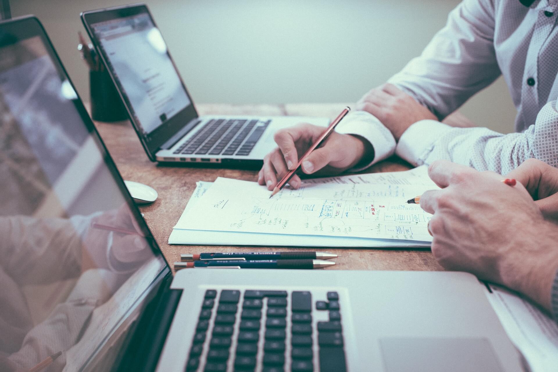 מחשבים ניידים ומסמכים על שולחן ויד רושמת עם עט